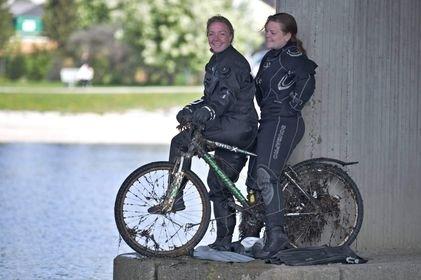 Ella Slapgård og Emma Maria Solli med en av syklene som ble hentet opp av elva.