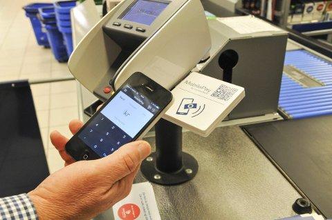 SLIK FUNGERER DET: Med MobilePay åpner en appen og sveiper mobilen inntil denne boksen som er montert ved kassaapparatet.