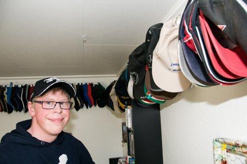 FAVORITTEN:– Akkurat nå er det caps'en jeg har på meg, som er favoritten, sier Andreas Hagen. Rundt 130 caps henger på skinner langs taket på rommet hans. Foto: Stine Solbakken.