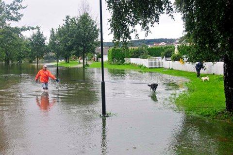 Vannet har bredd seg innover Bakkestranda og står tett ved boligene. Også deler av gangveien var torsdag formiddag dekket av vann.