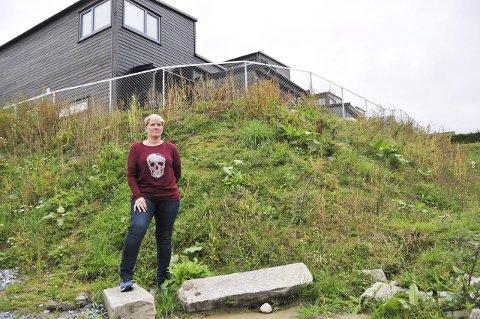 - BLE LOVET BEPLANTNING: Tonje Johannessen forteller at de ble lovet beplantning, men i skråninga nedenfor de nye boligene (i bakgrunnen) gror det foreløpig kun ugrass. foto: ørnulf holen