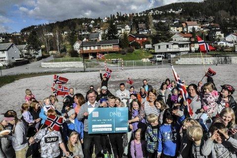 Stor dag: Tinnebyen og Omegn Velforening fikk en sjekk på 200 000 kroner av Sparebankstiftelsen. Nå skal lekeplassen i bakgrunnen rustes opp. Ikke rart flaggene kom fram for å markere feststemningen.