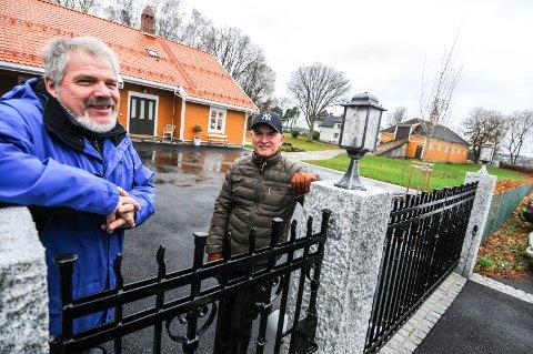 KAN VINNE: Arkitekt Finn Christiansen (til venstre) sammen med Georg Aubert på tunet i Håvundveien 58. Huset til venstre i bildet er nominert til årets byggeskikkpris. Huset er malt i Staverngul - som bygningen i bakgrunn. Også denne smijernsporten har de samme detaljene som hovedporten på gården. Også pipen er i gammel stil.