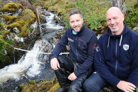Forskningsleder Anders Gjørwad Hagen (til venstre), og forsker Sigurd Hytterød ved Lågåsbekken hvor en av tre doseringsstasjoner for klor er plassert. Begge forskerne var også med i 2004 da Batnfjordselva ble behandlet med aluminium. Nå er det klor som utprøves.