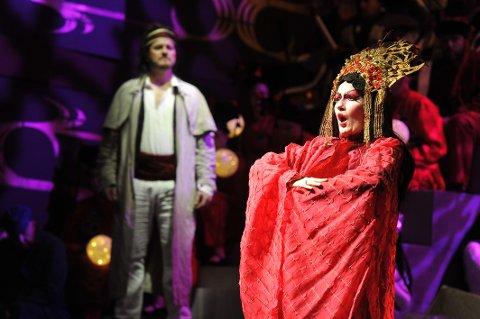 Prinsesse Turandot hater menn, og kapper av dem hodet når de ikke klarer å løse gåtene hennes. Det presset får Calaf (i bakgrunnen) kjenne på.