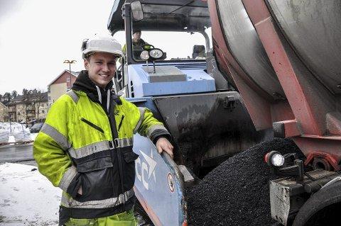 SVART HVERDAG: Lærling Bror Hemnes (20) fra Stavern jobber for at du kan kjøre på veier av god kvalitet – akkurat slik du forventer at det skal være. Her fylles asfaltmassen i utleggsmaskinen. Noen minutter senere er den blitt til et nytt, svart og slett dekke i en rundkjøring i Hønefoss sentrum.