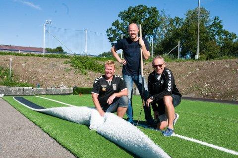 DUGNADSGJENG: Agnar Svendsen (t.v.), Espen Solemdal og Svein Gunnar Førsund iferd med å legge det nye kunstgresset på FK Eik Tønsbergs nedre bane. - 800 timer, anslår Svendsen den totale dugnadsinnsatsen til.