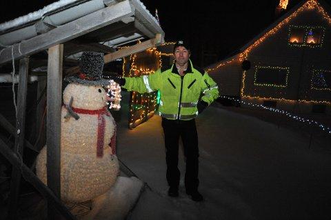 LYSKJENNER:Kristian Mathiesen med en av sine mange installasjoner i hagen nord for Åneby; lysende snømann med lysende polkagris.