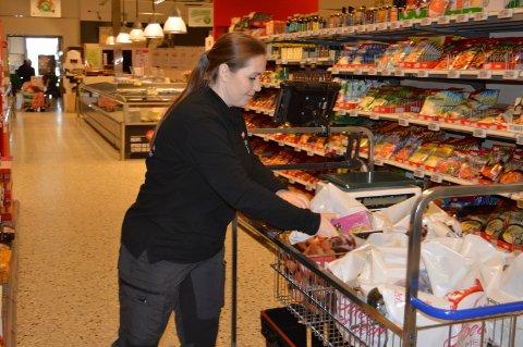 PLUKKER VARER: Datamaskinen fører Eva Stensrud effektivt mellom reolene for å plukke varer til bæreposene.