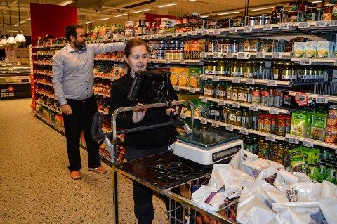 PLUKKER VARER: Datamaskinen fører Eva Stensrud effektivt mellom reolene for å plukke varer til bæreposene. I bakgrunnen butikksjef Aleksander Christoffersen.
