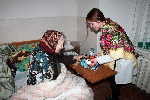 Sykepleiestudenter deler ut søtsaker og godteri til pasientene på hospitset for dødssyke i Dubno julaften 6. januar.