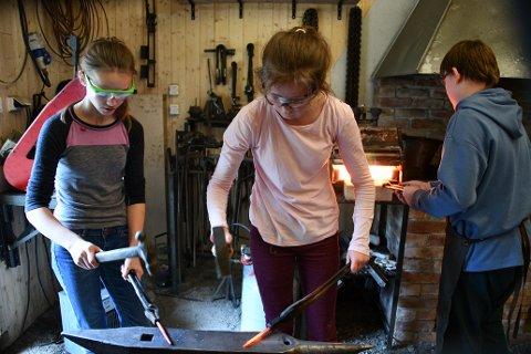 Hanna t.v og Margrete begynner å få sving på arbeidet med hammer og ambolt, mens Daniel sørger for å holde jernet varmt. Foto: Trond Folckersahm