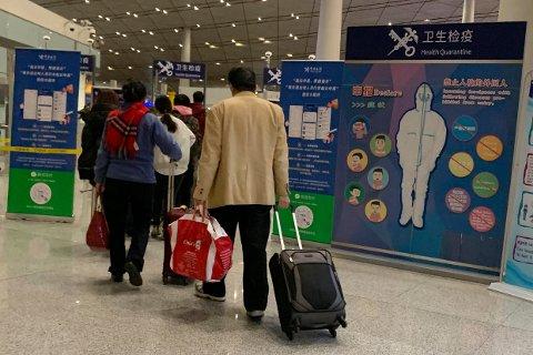 Reisende til Beijing i Kina blir møtt med informasjonsplakater om det nye lungeviruset som så langt ha krevd fire liv. Folkehelseinstituttet utelukker ikke at det kan komme til Norge. Foto: AP / NTB scanpix