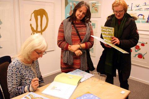 BOKSIGNERING: Grafiker, illustrartør og barnebokforfatter Eli Hovdenak signerer bøkene til Vigdis Hammerstad. Marit Anna Evanger lot seg begeistre av tegningene av Jippi.