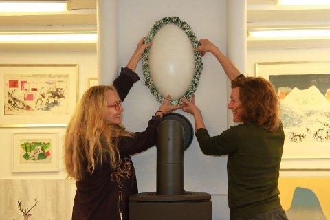 BROSJE I PORSELEN: Porselenbrosjen er 60 centimeter høy. Astri Grue er mesteren bak verket. Helga Storbekken i Røros Kunstformidling gleder seg til å vise fram Grues kunst under salgsutstillingen som åpner på lørdag. Den grønne kransen rundt er laget av organiske materialer: inntørkete blomster, kvann, lav og trollkjerringkoster som vokser på trær. - Kobber-, jern-, okerfarger gir farge til porselenet som brennes i flere omganger, forteller kunstneren.