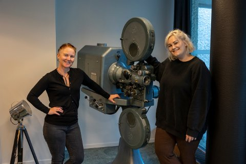 INVITERER TIL FILMSKOLE: F.v Kulturhusleder Myfanwy Moore og kinosjef Kristine Aas gleder seg til å fylle filmskole kurset ved sommerskolen. Her viser de fram et gammelt apparat som tidligere ble brukt for å vise film i Ås kino.