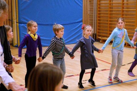KONSENTRERTE: 3.-klassingene Kristine, Julija, Nikolai og Thilie lærer tradisjonelle ringdanser på SFO, under ledelse av pensjonister fra Folkedansgruppen Bæringen.