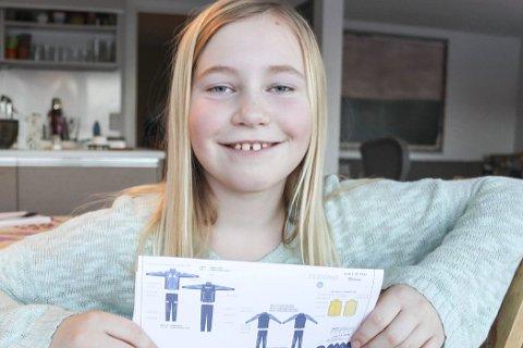FORNØYD VINNER: Oda Backe Hudalen leverte inn et forslag til hvordan det nye treningstøyet til Hope Idrettslag kunne se ut. Hun var ikke alene om å komme med forslag, men det var 9-åringen som vant konkurransen. Her viser hun med vinnerforslaget.