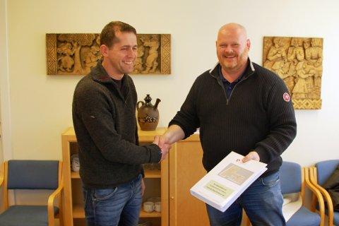 Håndtrykk til 21 millioner: Prosjektleder Tomas Aanonsen (til venstre) i Vågårshei kommune gratulerer en fornøyd Bernt Olav Mesel med kontrakten om byggingen av den nye skolen på heia.foto: Privat.