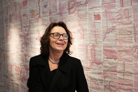 Mønsterbrudd: Tekstilkunstner Åse Ljones foran teppet med mønster fra hennes lårhalsbrudd.