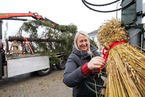 Marianne Beisland Rees hengte tirsdag formiddag opp julenek på torvet. I bakgrunnen ligger julegrana klar på kommunens lastebil.