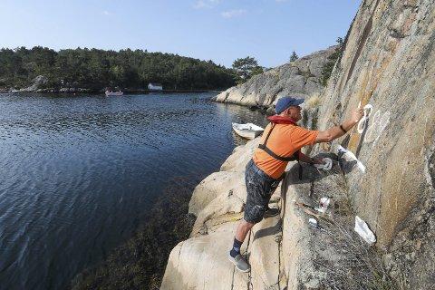 Males opp: Her står Kjell Skarheim på ei berghylle ved Østre Randvik og maler opp vannstandsmerket fra 1889. Det er 30 år siden merket sist ble malt. ALLE FOTO: Stig Sandmo