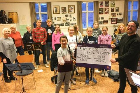 GLADE TONER: Dirigent Eirik Dørsdal (til høyre) og resten av musikantene i skolekorpset viser fram sjekken som Signe Leonore Lindstøl og Dagny Mortensen (til venstre i bildet) kom med på øvinga i Musikkens hus.