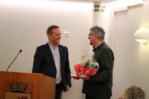 TAKK OG BLOMSTER: Jan Kåre Hansen (H) og prosjektleder Terje Aamot har vært i samme arbeidsgruppe i forbindelse med fjordryddingen. Hansen takket Aamot for innsatsen på bystyret før helgen.