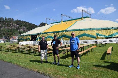 KRISEPAKKE: Eivind Egeli, Kåre Bakke og Henrik Birkeland foran det gedigne teltet på en tidligere Sirafestival. Det kan ta 5000 mennesker. Så mange ble det ikke på Sira denne sommeren. Foto: Erik Thime