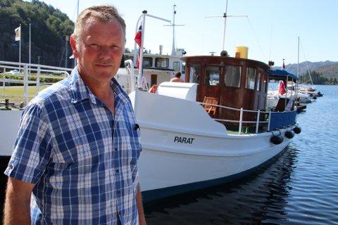 BÅTEIEREN: Oddvar Oma foran stålbåten «Parat» fra 1893. Han har selv bygget den om fra et enkelt skrog som ikke hadde stort annet enn ror og propell til en flott lystbåt.