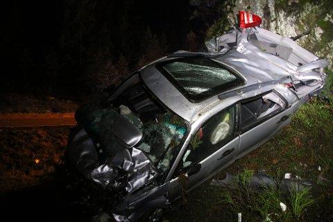 KRAFTIG SMELL: Restene av bilen viser at det har vært store krefter i sving da bilen traff lyktestolpe, grantre og til slutt havnet på taket opp mot fjellveggen.