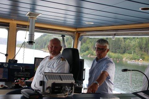 PÅ BROA: Kaptein Arnfinn Jensen på Hidraferja fikk besøk av fylkesordfører Arne Thomassen (H) i sommer. Fylkesordføreren sa at han skulle jobber for fastlandsforbindelse både til Hidra og Andabeløy. Nå er imidlertid Thomassen enig med fylkesadministrasjonen i at man bør vente med nye bergeninger.