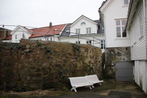 GARASJE: Bak muren er det et stort areal fylt med sand og grus som kan utnyttes som P-plasser.