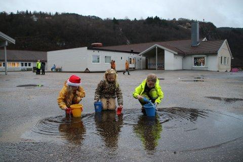 GRAVER I VANN: Noen av elevene på Liknes barneskole lekte i går i en av vanndammene på skoleplassen. Det ser ut som det bare blir nedbør i flytende form i bøttene frem til jul i år.