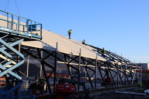 I STROPPEN: Montørene fra AK Mekaniske henger bokstavelig talt i stroppen for å få taket på plass på Flekkefjord Sparebank Arena. Tekking og isolering av tak og vegger skal foregå nå frem til påske.