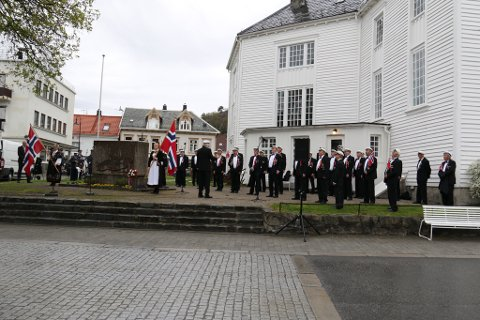 STO TIDLIG OPP: Flekkefjord Sangforening var aktive på 17. mai, og gjennomførte fem opptredener. Her ved minnestøtten utenfor Flekkefjord kirke.