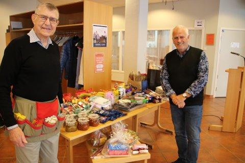 GODT FORNØYD: Tobias Salmelid med åreforkle  for loddsalg og Per Stordrange i husstyret til Flekkefjord Bedehus, var godt fornøyd med at det igjen er mulig å arrangere basar.