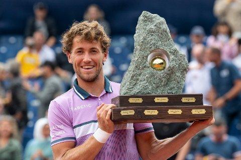 Casper Ruud gliser med trofeet han fikk for ATP-triumfen i Gstaad. Den seieren må han legge kjapt i glemmeboka. Foto: Peter Schneider / Keystone via AP / NTB