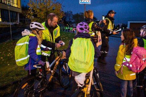 Brannsjef Karl Johannes Romarheim deler ut nye lys til syklistar på skuleveg under TSU sin refleksaksjon sist fredag.