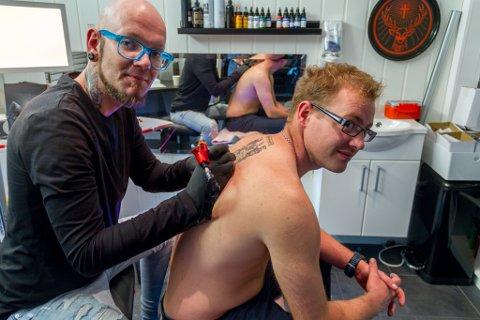 Tatovør Tommy Råen er overraska over kor stor pågang det har vore etter at han og kona opna tatoveringsstudiet i april. Her tatoverer han eit famileskjold på ryggen til Frode Harris - ei tatovering dei fire brørne hans også skal ta.