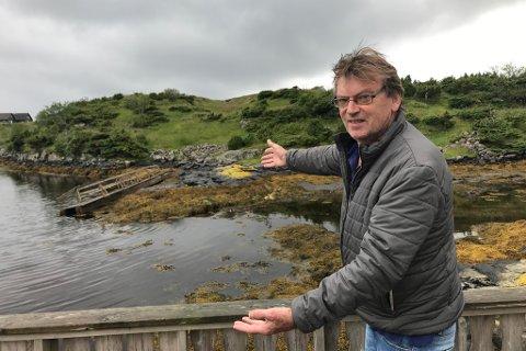 I FJÆRA: Deler av brua hamna på land. Bjørn Misje viser fram korleis det ser ut etter at flodbølga besøkte Svanholmen i Gulen.