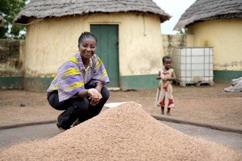 Pearl Florence Hamre på plass nord i Ghana, framfor ein haug med oppmalte frø som skal bli sheasmør.