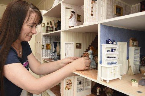 1 DET HVITE HUS: Trine Angelsens dukkehus har fått navnet «Det hvite hus» og inneholder alt et hus trenger. Legg merke til det blå serviset i hyllen. 2 UHELDIG: Dina fra den nyeste serien Breidablikk er en uheldig person og har veltet epler på gulvet. 3 BIBLIOTEK: Huset har også fått et eget bibliotek. 4 DETALJER: De små parfymeflaskene i moteforretningen, har Trine laget av millimeter store perler som hun har limt sammen.