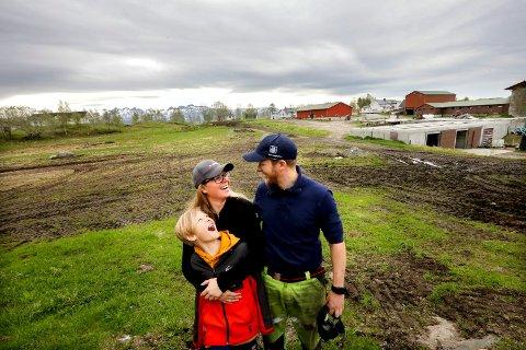 Øyvor og Svein Magne Åsbakk, med Johnas (9) på tomta der det nye grisefjøset skal stå. Roald (8) var  ikke til stede da AN besøkte gården.