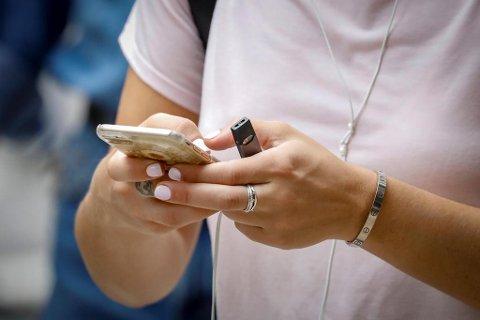NY TREND: En kvinne holder en Juul i hånden. Denne typen e-sigarett har blitt svært populær i USA. Foto: Brendan Mcdermid (Reuters)