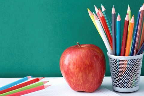 Image of crayons and red apple against blackboard