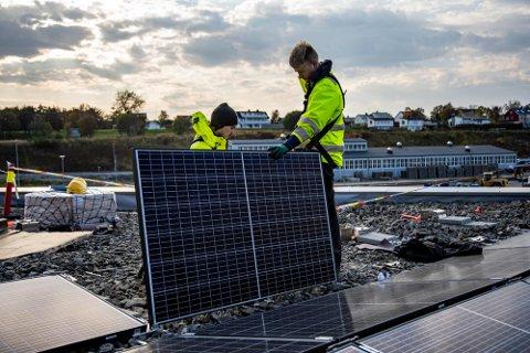 Montør Arve Austvik og lærling Lucas Bendiksen i elektrogruppen monterer solcellepaneler på taket på Energihuset.