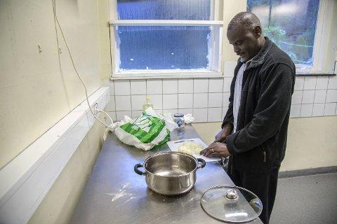 Faisa (40) skjærer opp løk til middagen på kjøkkenet ved asylmottaket på Klokkarvik.