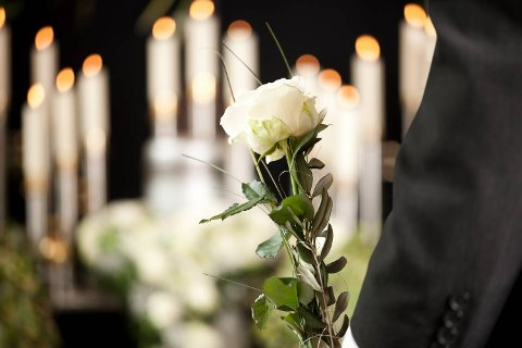Religion, death and dolor  - man at funeral with white rose mourning the dead; Shutterstock ID 136792436; PO: purchase_order4; Job: job1; Client: client2; Other: other3