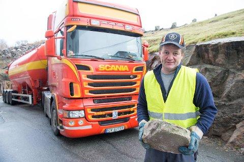 Torgils Rogne med steinen som raste ned på førerhuset hans på E16 tirsdag og landet på lasteplanet på tilhengeren. BA presiserer at bildet er tatt onsdag, og da hadde Rogne byttet ut tilhengeren med en tank. Foto: Magne Turøy